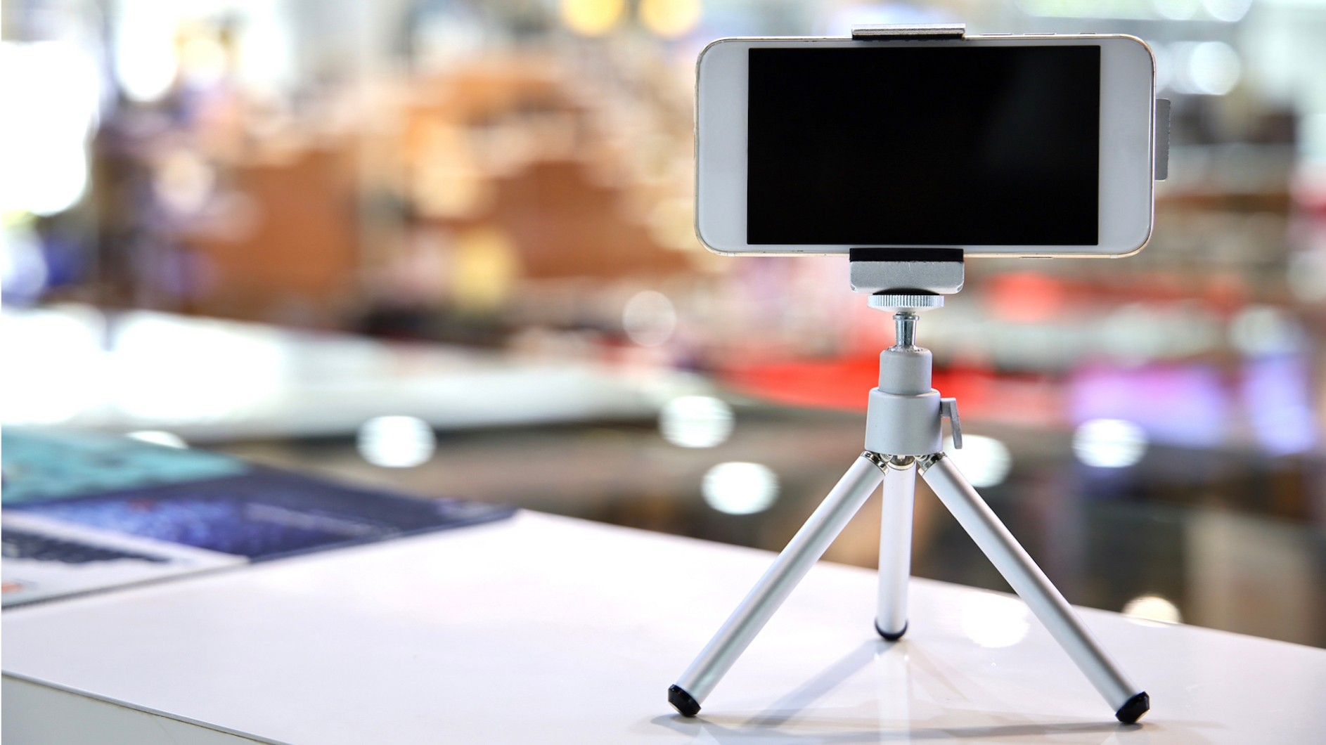 Smartphone on mini-tripod on a desk in front a blurry background